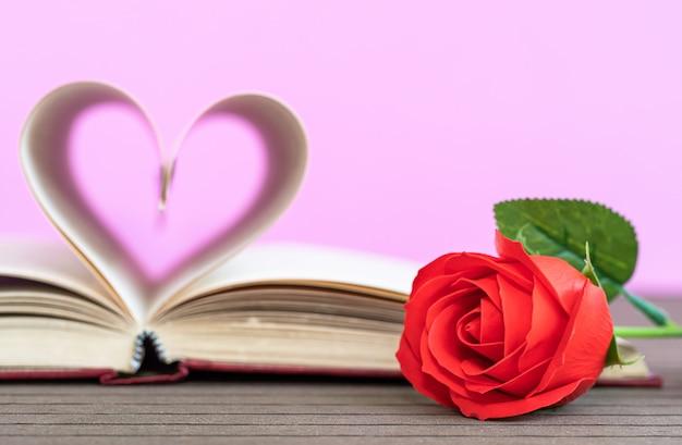 曲がったハートと赤いバラの本のページ