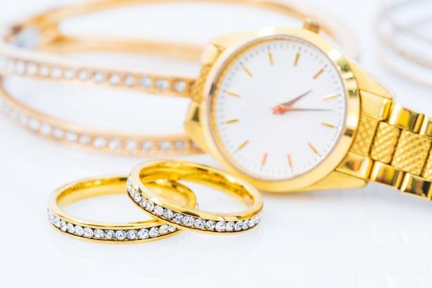 Роскошные золотые кольца и женские золотые часы на белом