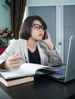 Женщина работает на ноутбуке в домашнем офисе