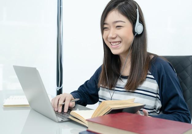 Студент сидит в гостиной и учится онлайн