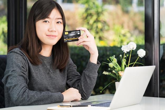 デッキ上のラップトップコンピューターでクレジットカードを保持している若い女性