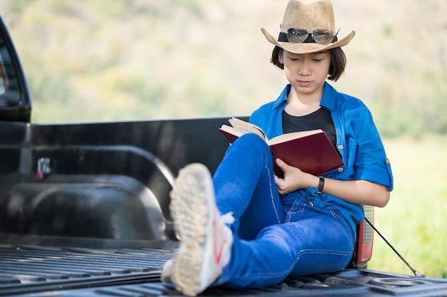 女性は帽子をかぶって、ピックアップトラックで本を読んで
