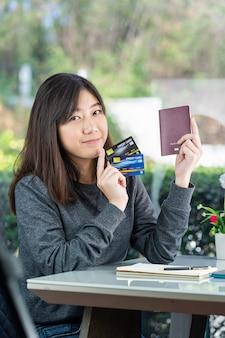 パスポートとクレジットカードを示す座っている若い女性