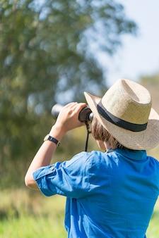 女性、帽子を身に着けて、草地で両眼を持っている
