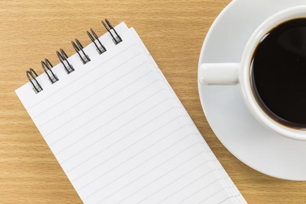 木製テーブル上のコーヒーとメモ帳