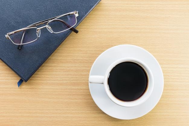 木製デッキと眼鏡のコーヒーカップ