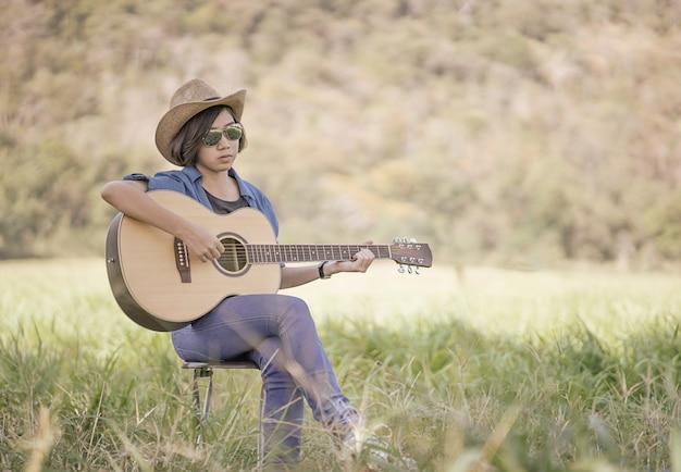 女性の短い髪の帽子とサングラスは芝生のフィールドでギターを弾く