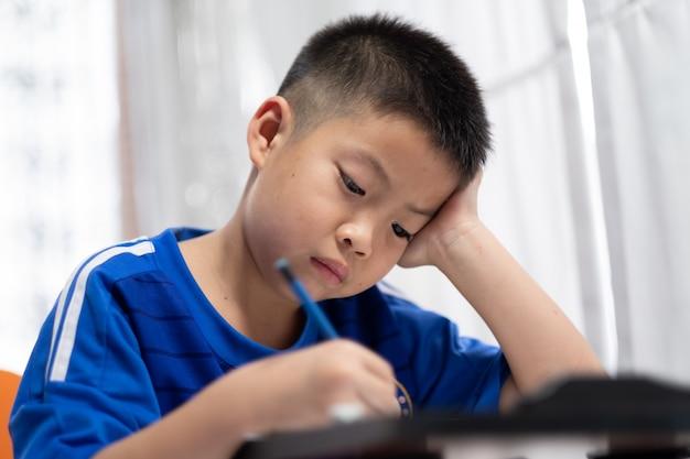Дети мальчик делает домашнее задание, малыш написать бумагу, концепция семьи, время обучения, студент, обратно в школу