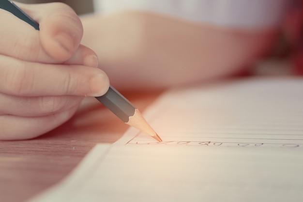 Дети девочка делает домашнее задание, малыш пишет бумагу, концепция семьи, время обучения, студент, обратно в школу