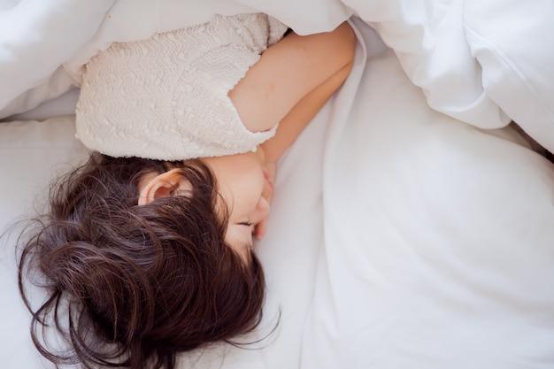 Азиатская девушка спит на кровати, ребенок болен, ребенок спит