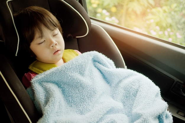 子供は車で寝ます、子供は気分が悪く、車の座席で寝ます