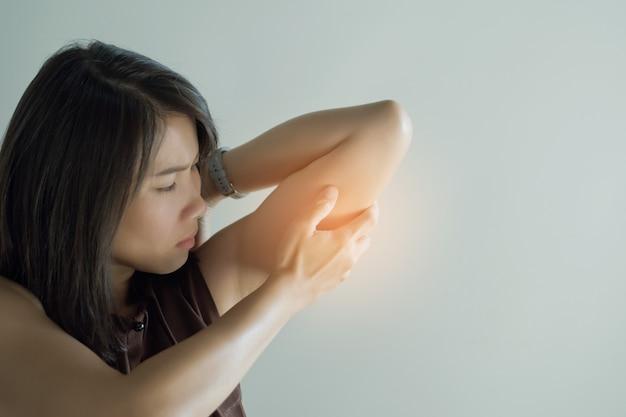 アジアの女性の肘の痛み、白い背景の上の少女の肘の痛み