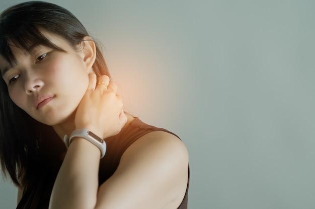 アジアの女性の首の痛み、白い背景の上の少女の首の痛み