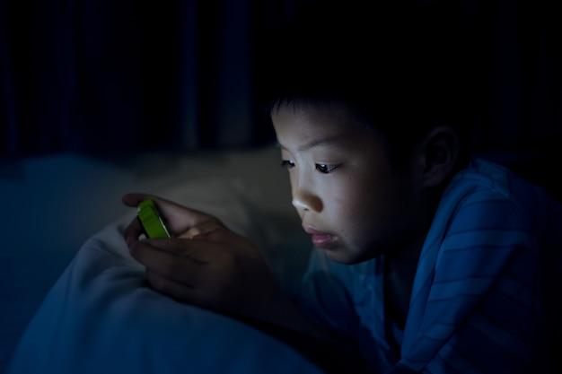 Азиатский китайский мальчик играет смартфон на кровати с шумом и мягким фокусом