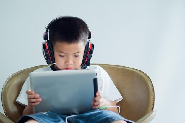 Азиатский китайский мальчик, играющий в планшет, увлеченный игрой и мультфильм,