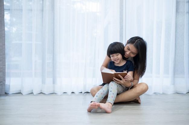 母はベッドで彼女の子供のための本を読んで、漫画の本を読んで、子供たちとお話