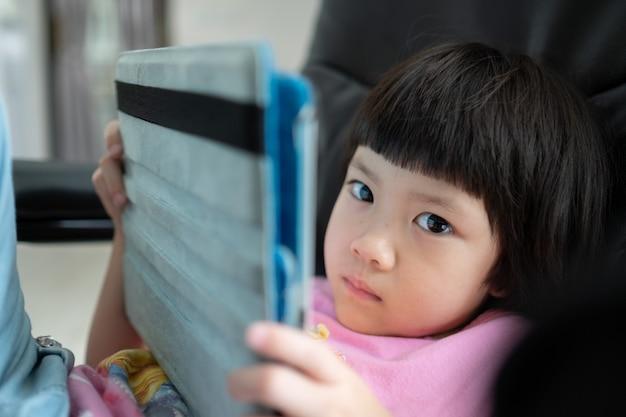 中国の子供中毒電話、スマートフォンを遊んでいるアジアの女の子、子供が電話を使用、漫画を見て