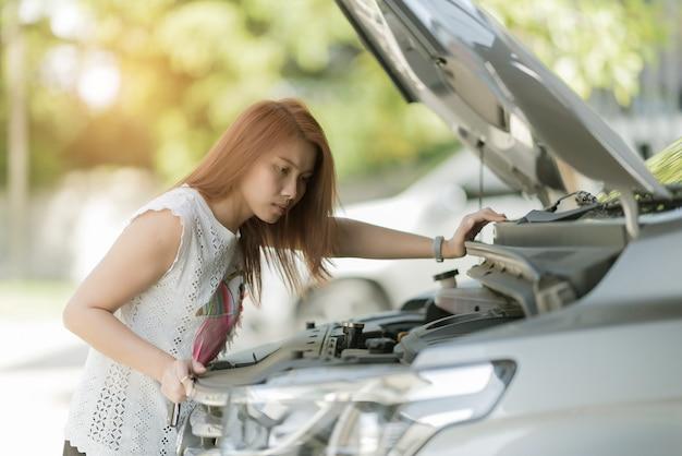 車のオイルレベルをチェックする女性、オイルカーを交換する