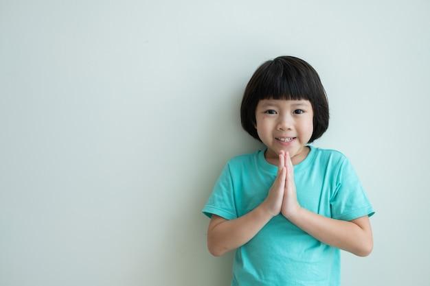敬意を表すアジアの女の子、タイの子供は敬意を払う