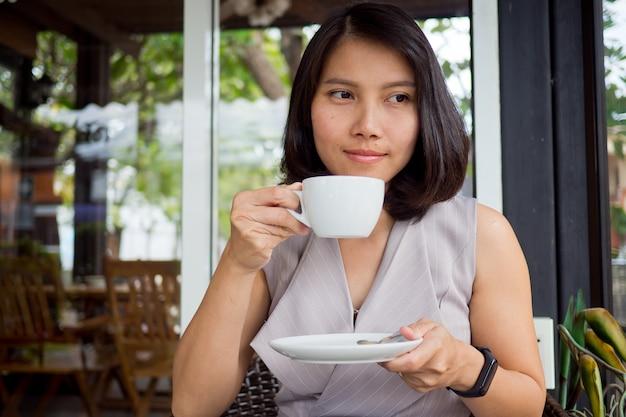 ホットコーヒーを飲む女性、時間をリラックス
