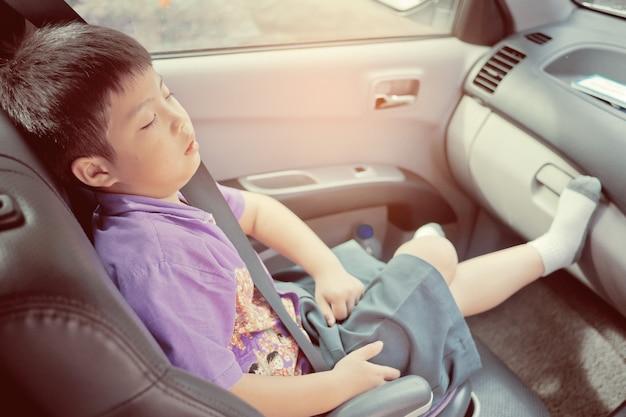 子供は車の上で寝、子供は気分が悪く、車の座席で寝る