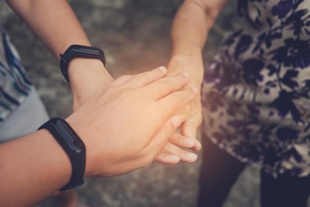 一緒に手を取り合って、調和して、一緒に働いて、チームワーク、手を握りしめて、団結を示す