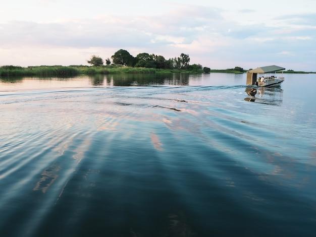 夕日時に水脈が激しく激しく蛇行川でモーターボートを運転する