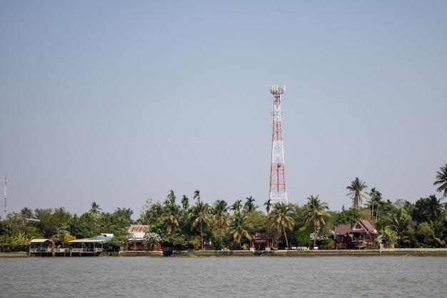 Башня связи в деревне у реки с голубым фоном облачного неба