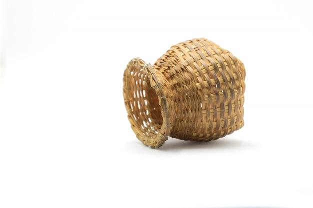 Бамбуковая корзинка ручной работы. используется для размещения различных устройств на белом фоне.