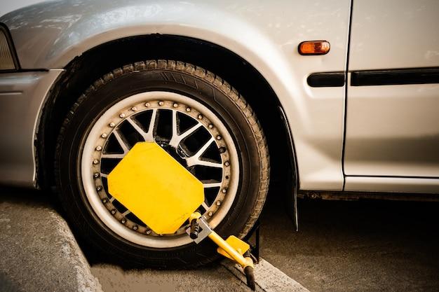 自動車は、不法駐車された自動車の前輪が固定されている。