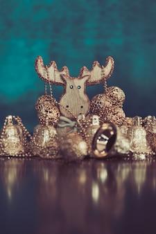 ゴールデンクリスマスボールとターコイズの木製鹿とベルの飾りのコレクション