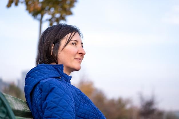 Вдумчивый красивая женщина с каштановыми волосами, сидя в одиночестве на открытом воздухе