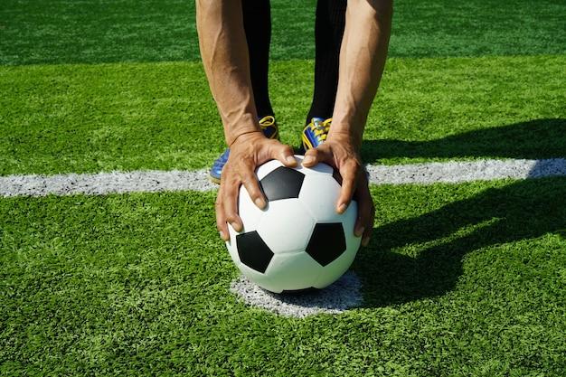 緑の芝生とスタジアムでサッカーボール