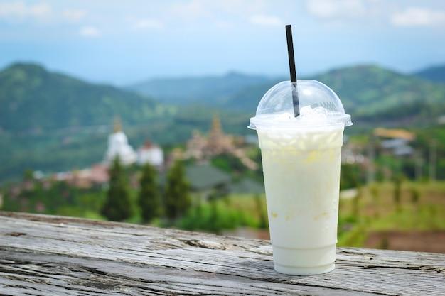 自然の木のテーブルのプラスチックカップのアイスミルク