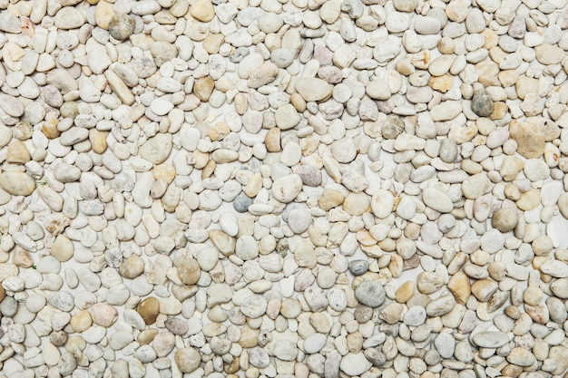 小さな自然に磨かれた白い岩石の小石の背景