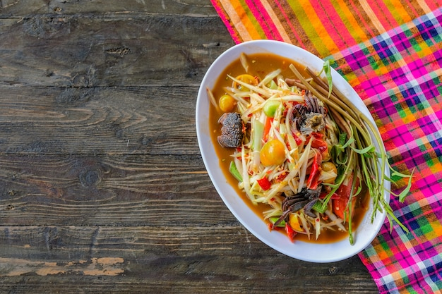 ソムダム(スパイシーパパイヤサラダ)、塩漬けのカニ、木製テーブル(タイ料理)