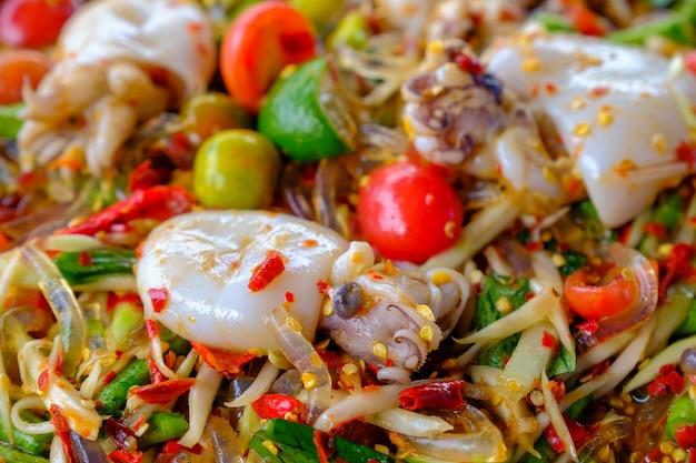 ソムタムシーフード(スパイシーパパイヤサラダ)、塩漬けイカ、木製テーブル(タイ料理)