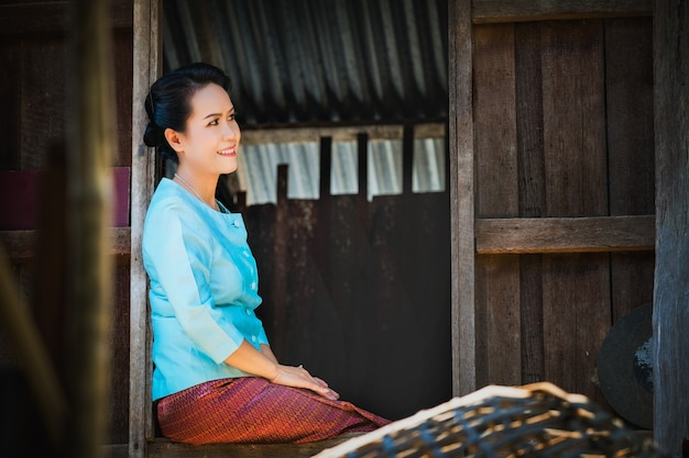 朝の窓の前に青い服を着た村人たち。