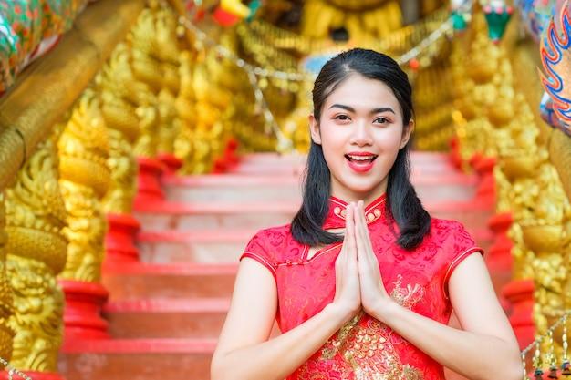 女性は赤いドレス中国スタイル手 - ハローを身に着けている。