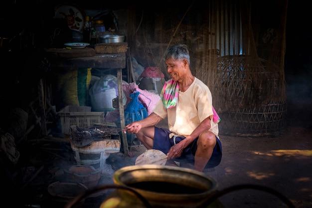 年上の男性は、タイ農村部の木炭ストーブで魚を焼いています。