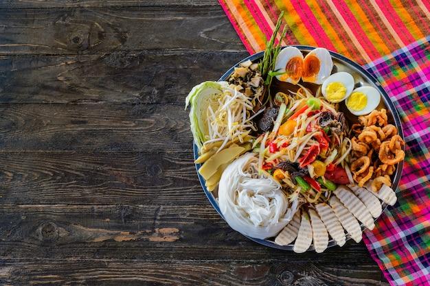 暗いテーブルの背景にソムタムやパパイヤのサラダ。タイ料理のコンセプト