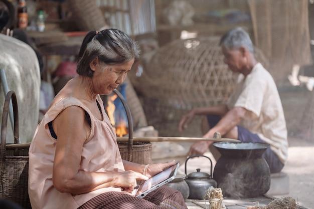 アジアの老婦人たちはタイ農村でタブレットをしています。