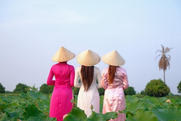 アジアの女の子は蓮の庭に立っています。