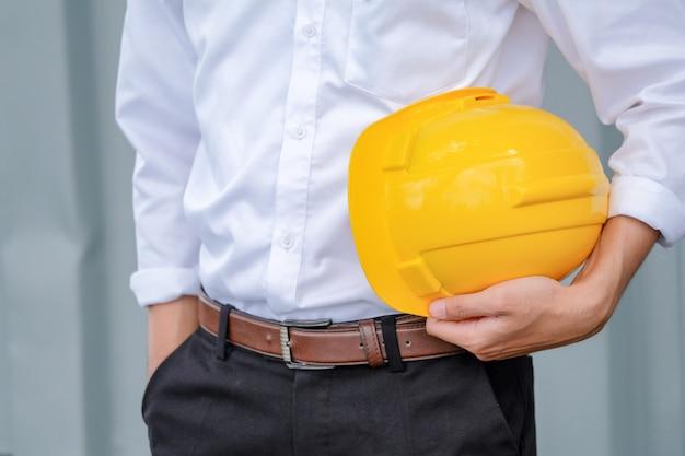 Мужчина держит желтый шлем крупным планом