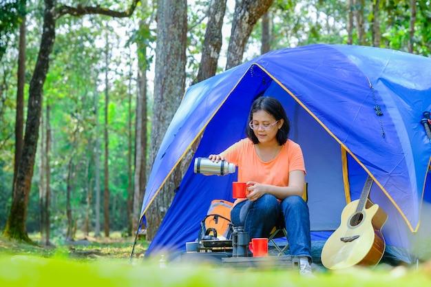 アジアは森の中でキャンプテントを広げながら移動します。