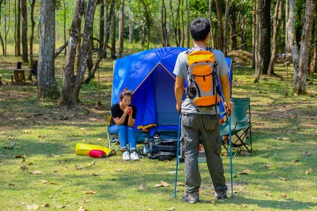 Счастливый азиатский рюкзак мужчины и женщины в парке и предпосылке леса