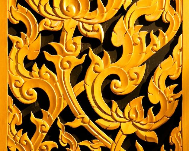 タイの寺院の木製の窓を刻んでいる古代の黄金。タイ