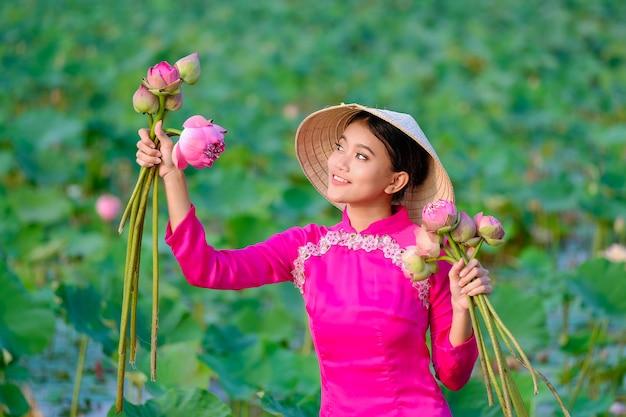ベトナム人女性は日没時にロータスを集めています。