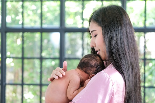 彼女の肩にもたれて、生まれたばかりの赤ちゃんを持つアジアの母