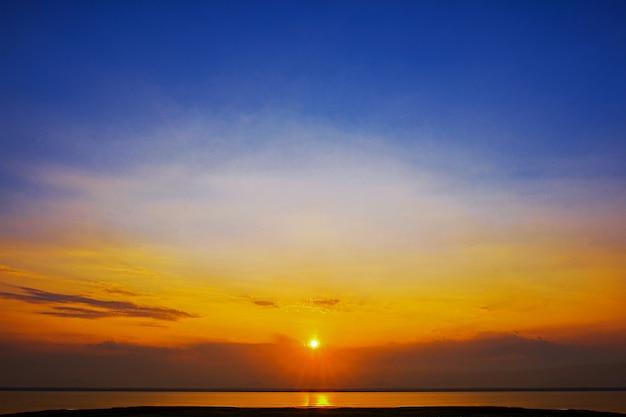 壮大な劇的な夕日の背景の美しい黄色オレンジと青の色の夕焼け空。